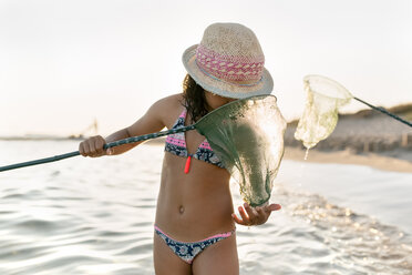 Spain, Menorca, girl with a dip net on the beach - MGOF03165