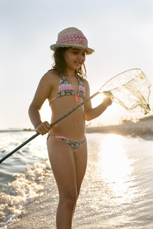 Spain, Menorca, girl with a dip net on the beach - MGOF03168