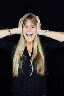 Portrait of screaming blond woman with head in hands in front of black background - CHAF01804