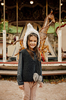 Portrait of smiling little girl wearing fur hat standing in front of children's carousel - CHAF01813