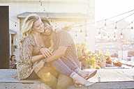 Happy couple sitting on rooftop, embracing each other - WESTF22827