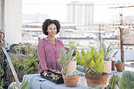 Smiling woman standing in her rooftop garden - WESTF22833