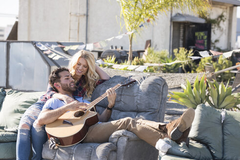 Couple on rooptop sitting on sofa and playing guitar - WESTF22842