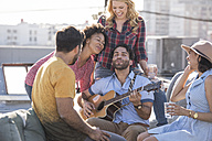 Friends having a rooftop party and playing guitar - WESTF22854