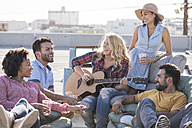 Friends having a rooftop party and playing guitar - WESTF22860