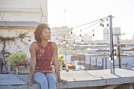 Young woman sitting on rooftop terrace, enjoying the sun - WESTF22875