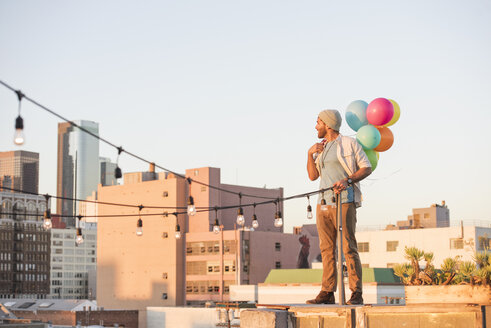 Young man standing on rooftop, holdng balloons - WESTF22890