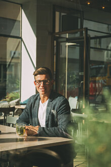 Smiling man sitting in a coffee shop with glass of tea - CHAF01819