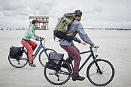 Germany, Schleswig-Holstein, St Peter-Ording, couple riding bicycle on the beach - RORF00714
