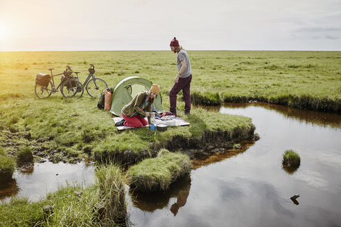 Germany, Schleswig-Holstein, Eiderstedt, couple with bicycles camping in marsh landscape - RORF00717