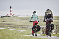 Germany, Schleswig-Holstein, Eiderstedt, couple riding bicycle near Westerheversand Lighthouse - RORF00720
