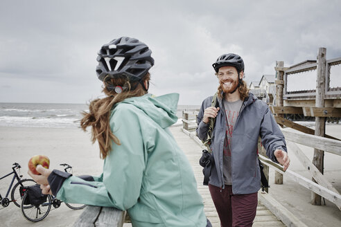 Germany, Schleswig-Holstein, St Peter-Ording, couple on a bicycle trip having a break on jetty at the beach - RORF00723