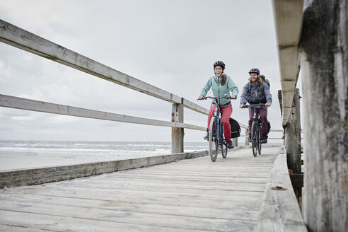 Germany, Schleswig-Holstein, St Peter-Ording, couple riding bicycle on jetty at the beach - RORF00726