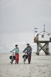 Germany, Schleswig-Holstein, St Peter-Ording, couple pushing bicycles on the beach - RORF00729