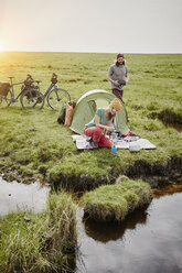 Germany, Schleswig-Holstein, Eiderstedt, couple with bicycles camping in marsh landscape - RORF00735