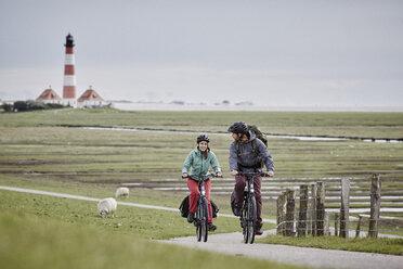 Germany, Schleswig-Holstein, Eiderstedt, couple riding bicycle near Westerheversand Lighthouse - RORF00741
