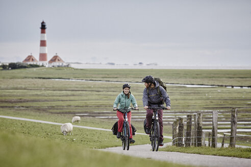 Germany, Schleswig-Holstein, Eiderstedt, couple riding bicycle near Westerheversand Lighthouse - RORF00741