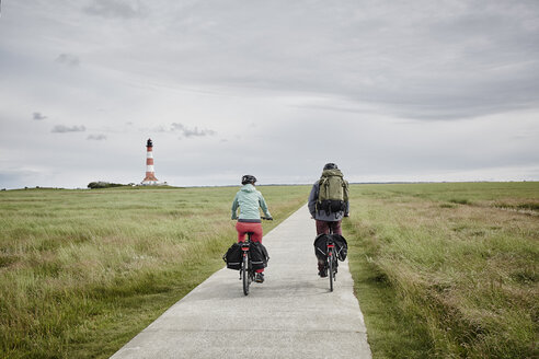 Germany, Schleswig-Holstein, Eiderstedt, couple riding bicycle near Westerheversand Lighthouse - RORF00744