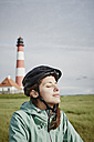 Germany, Schleswig-Holstein, Eiderstedt, woman wearing bicycle helmet relaxing near Westerheversand Lighthouse - RORF00747