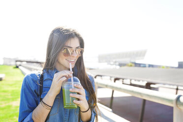 Spain, Barcelona, portrait of smiling young woman with green beverage - VABF01270