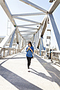 Spain, Barcelona, smiling young woman with beverage walking on a bridge - VABF01273