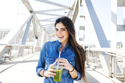 Spain, Barcelona, portrait of smiling young woman with beverage on a bridge - VABF01276