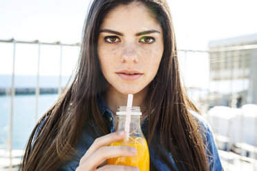 Portrait of young woman with glass bottle of orange juice - VABF01279