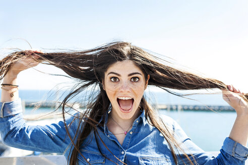 Portrait of screaming young woman pulling her hair - VABF01282