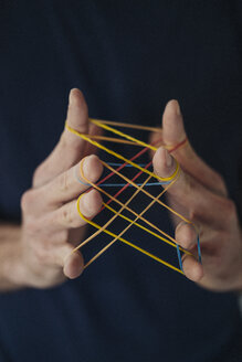 Close-up of man holding rubber bands - KNSF01200