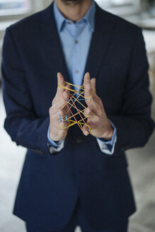 Close-up of businessman holding rubber bands - KNSF01203