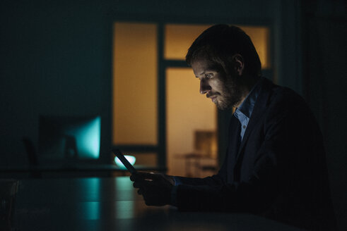 Businessman working late in office using tablet - KNSF01212
