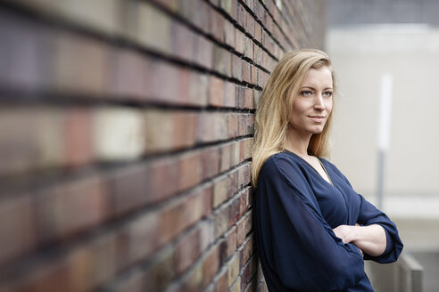 Portrait of smiling blond young woman leaning against brick wall - DMOF00004