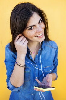 Portrait of smiling young woman with earphones and smartphone in front of yellow background - VABF01286