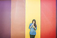 Smiling young woman in front of colourful striped wall drinking orange juice - VABF01289
