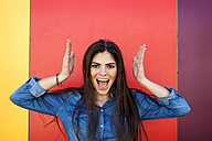 Portrait of screaming young woman in front of colourful wall - VABF01292