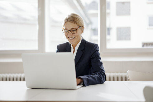 Smiling businesswoman using laptop in office - JOSF00701