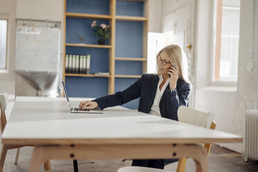 Businesswoman using laptop and cell phone in office - JOSF00704