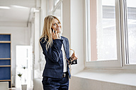 Portrait of smiling businesswoman on cell phone in office - JOSF00707