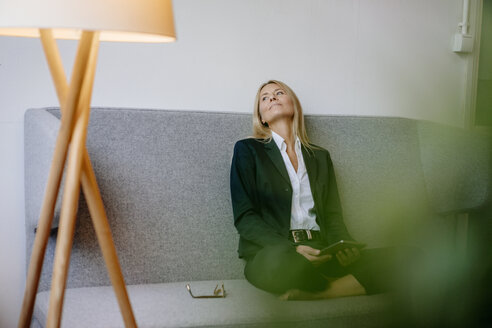 Relaxed businesswoman sitting on couch holding tablet - JOSF00713