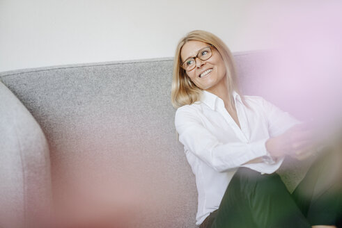 Smiling relaxed businesswoman sitting on couch - JOSF00716