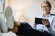 Businesswoman sitting down using tablet - JOSF00722
