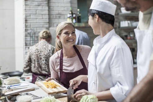 Student in cooking class smiling at female chef - ZEF13524