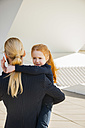 Businesswoman on the phone holding daughter - CHAF01836