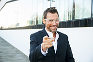 Portrait of confident businessman outdoors pointing his finger - CHAF01860