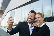 Smiling businessman with woman taking a selfie - CHAF01863