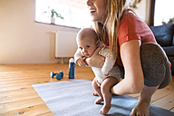 Smiling mother with baby and dumbbells at home - HAPF01367