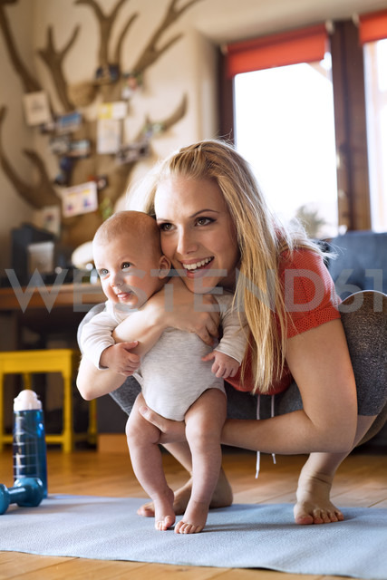 Smiling mother with baby and fitness equipment at home - HAPF01370 - HalfPoint/Westend61
