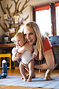 Smiling mother with baby and fitness equipment at home - HAPF01370