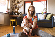 Smiling mother with baby exercising with dumbbell at home - HAPF01373