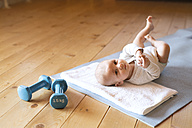 Baby at home lying on mat next to dumbbells - HAPF01376